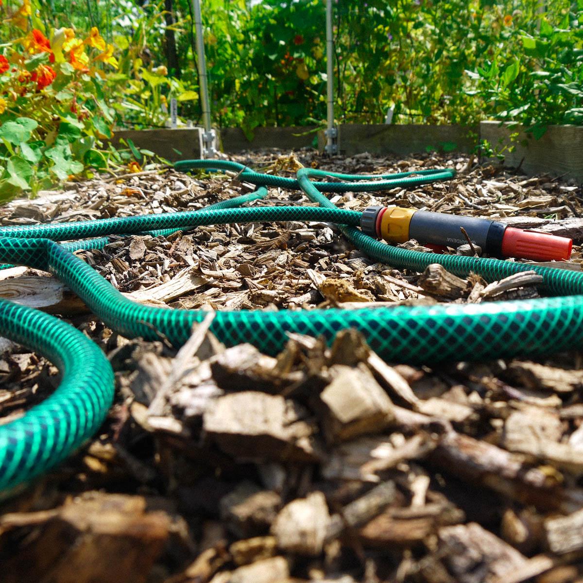 De zon maakt het water in de tuinslang erg heet
